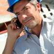 Stock Photo: Engineer with blue security helmet talking on mobile phone