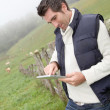 Breeder using electronic tablet in field — Stock Photo