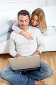 Happy couple surfing on internet at home — Stock Photo