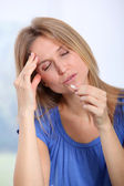 Woman taking pills to ease migraine — Stock Photo