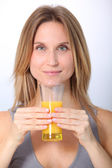 Closeup of beautiful blond woman drinking fruit juice — Stock Photo