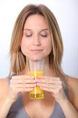 Closeup of beautiful blond woman drinking fruit juice — Stock Photo