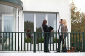 Couple and real-estate agent in front of house for sale — Stock Photo