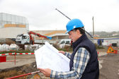Engineer on construction site with building plan — Stock Photo