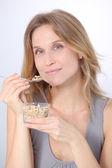 Closeup of beautiful blond woman eating cereals — Stock Photo