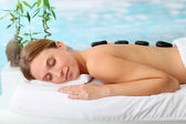 Beautiful woman with hot stones on her back — Stock Photo