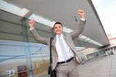 Smiling businessman with arms up — Stock Photo