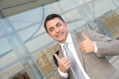 Businessman standing outside modern building — Stock Photo