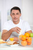 Smiling adult man having breakfast — Stock Photo