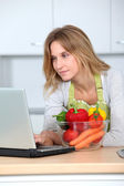 Woman in kitchen looking for cooking receipe — Stock Photo