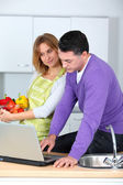Couple in kitchen looking for cooking receipe — Stock Photo