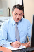Salesman working in front of computer — Stock Photo