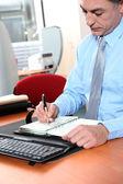 Uomo d'affari alla sua scrivania scrivendo sulla sua agenda — Foto Stock