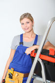 Smiling electrician woman standing by scale — Stock Photo