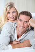 Smiling couple laying on sofa — Stock Photo
