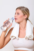 Blond woman drinking water after exercising — Stok fotoğraf