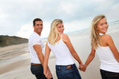 Family walking hand to hand on a sandy beach — Stock Photo