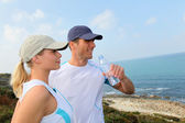 Couple drinking water after exercising — Stock Photo