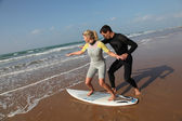 Man teaching young woman to surf — Stock Photo