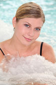 Beautiful woman bathing in jacuzzi of spa center — Stock Photo