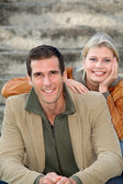 In loved couple sitting in staircase — Stock Photo