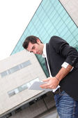Man using electronic tablet in front of modern building — Stock Photo