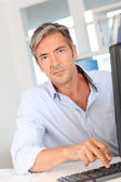 Man in office working on desktop computer — Stock Photo
