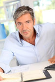 Handsome office worker writing notes on agenda — Stock Photo