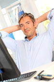 Man relaxing in office with stretched arms — Stock Photo