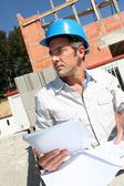 Entrepreneur checking plan on construction site — Stock Photo