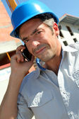 Engineer with blue security helmet talking on mobile phone — Stock Photo