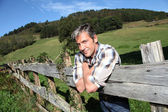 Portrait of handsome breeder leaning on fence — Stock Photo