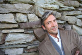 Man leaning on stone wall in countryside — Stock Photo