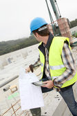 Construction manager using electronic tablet on site — Stock Photo