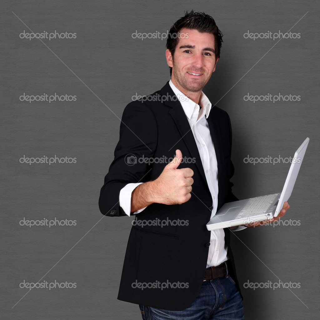 Salesman holding laptop computer and showing thumb up  Stock Photo #18257753