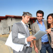 Real-estate agent showing house under construction to couple — Stock Photo #18261163