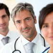 Portrait of doctor standing amongst medical team — Stock Photo