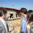 Real-estate agent showing house under construction to couple — Stock Photo #18261243