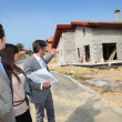 Стоковое фото: Real-estate agent showing plan to young home investors