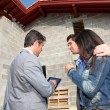 Real-estate agent showing house under construction to couple — Stock fotografie
