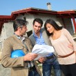 Entrepreneur showing house under construction to couple — Stockfoto