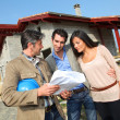 Entrepreneur showing house under construction to couple — Stock Photo #18261287