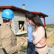 Entrepreneur showing house under construction to couple - Stock Photo