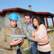 Foto Stock: Entrepreneur showing house under construction to couple