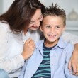 Little blond boy sitting on sofa with his mother — Stock Photo