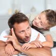 Father and son playing on sofa — Stock Photo