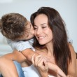 Stock Photo: Little boy kissing her mom