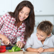 Mother cooking with son in kitchen — Stock Photo