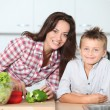 Mother cooking with son in kitchen — Stock Photo #18263063