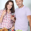 Couple drinking wine while fixing dinner — Stock Photo